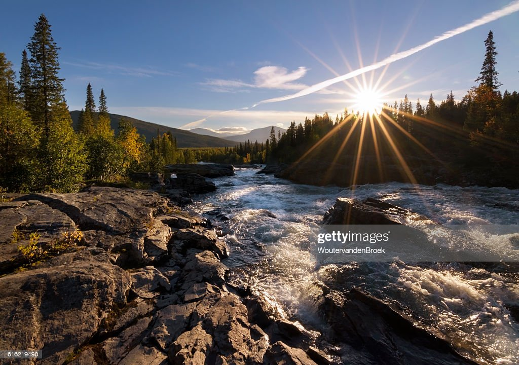 Sun with sun rays giving golden glow to river landscape : Foto stock