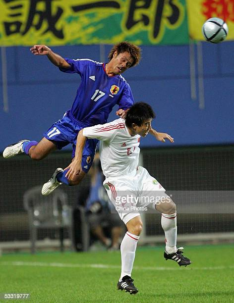Sun Xiang of China fights for a ball with Komano Yuichi of Japan during a match of the East Asian Football Championship on August 3, 2005 in Daejeon,...