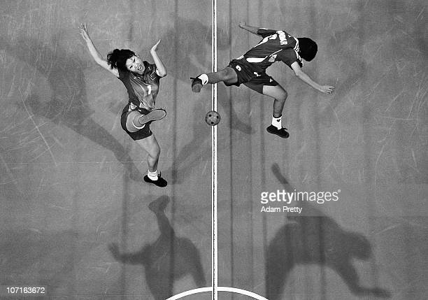 Sun Xiaodan of China kicks the ball past Than Phyu Phyu of Myanmar during the Womens Sepaktakraw Double final at Guangzhou Gymnasium during day...