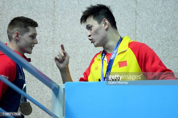 Sun Yang of China speaks with Duncan Scott of Great Britain during the medal ceremony for the Men's 200m Freestyle Final on day three of the Gwangju...