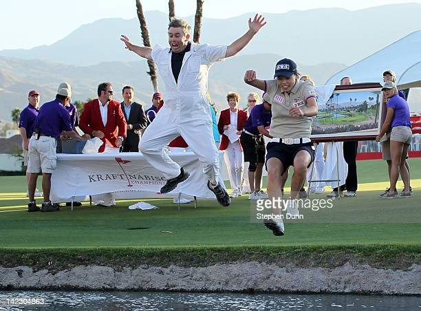 Sun Young Yoo of Korea and caddie Adam Woodward take the traditional leap into Poppy's Pond by the 18th green after Yoo won in a playoff during the...
