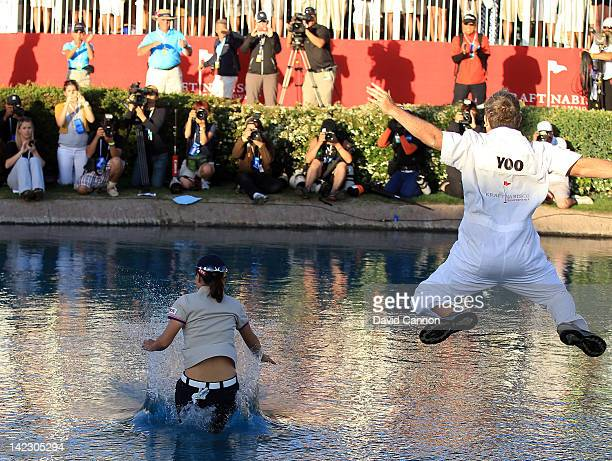 Sun Young Yoo of South Korea celebrates with her caddie Adam Woodward by jumping into 'Poppy's Pond beside the 18th green after her playoff win...