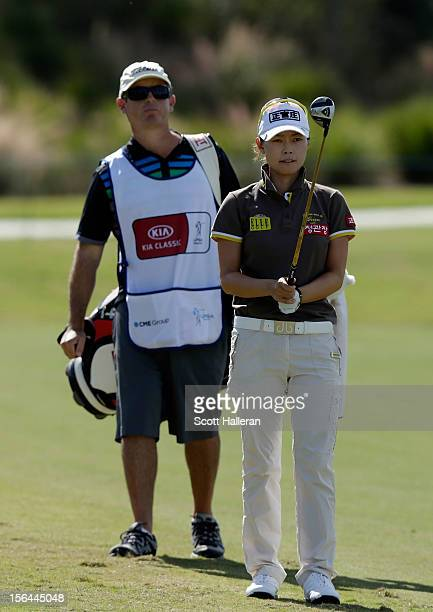 Sun Young Yoo of South Korea lines up a shot on the second hole with her caddie Adam Woodward during the first round of the CME Group Titleholders at...