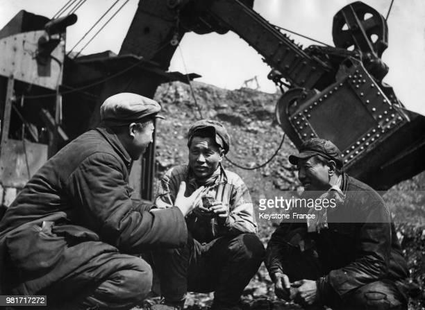 Sun Yutien et Wang Yungmao discutent avec le président du syndicat Yun Shuteh à la mine de charbon à ciel ouvert à Fushun en Chine le 28 avril 1955