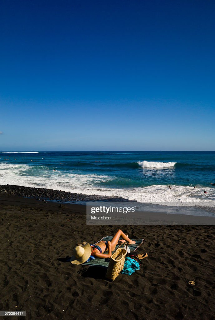 Sunbath on the black sand beach : Stock Photo