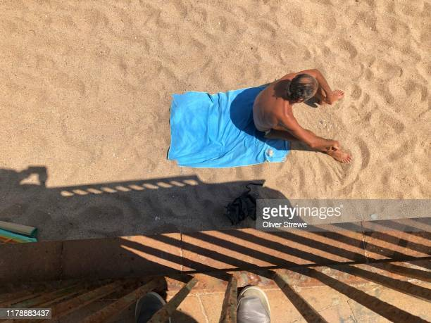 sunbather at beach - beach sunbathing spain stock pictures, royalty-free photos & images