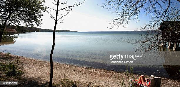 A sunbather enjoys the warm weather sitting at the beach of Ammersee Lake on April 16 in Stegen Germany The unseasonably warm weather has heralded...