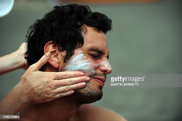 A sunbather has UV filter cream applied on his face at Matanzas beach in Navidad some 150 km southwest of Santiago Chile on February 12 2011 Solar...
