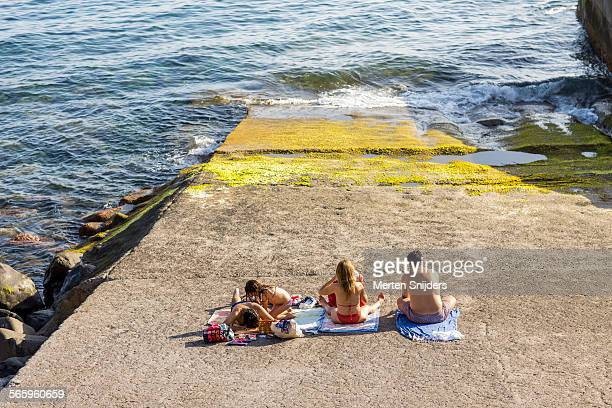 sunbathers at concrete boat ramp - merten snijders stock pictures, royalty-free photos & images