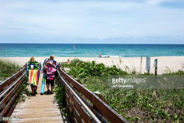 Sunbathers carrying chairs to the Hutchinson Island public beach.