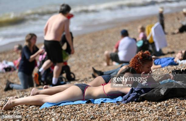 Sunbathers enjoy the beach as a spell of hot weather coincides with lockdown restrictions being eased on March 30, 2021 in Brighton, England....
