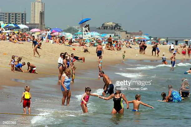 Sunbathers enjoy the cool waters of the Atlantic Ocean August 15 2003 in Bradley Beach New Jesrey New Jersey Governor James McGreevey urged New...