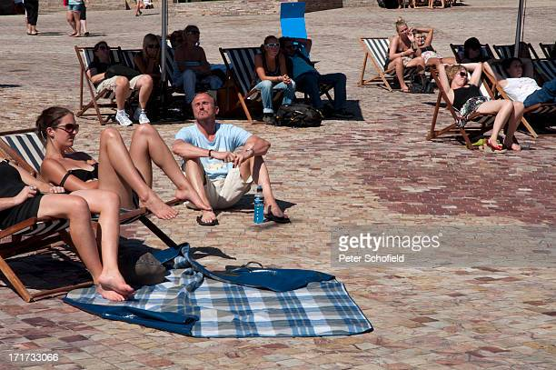 CONTENT] Sunbathers enjoy the heat in Federation Square Melbourne Australia January 2012 People in deck chairs lounge in the public square lazily...