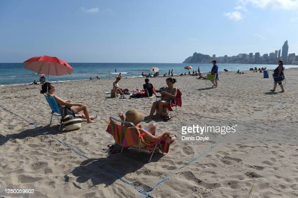 Sunbathers enjoy the sunny weather in their designated ropedoff areas on Poniente beach a day after the town's beaches were reopened after three...