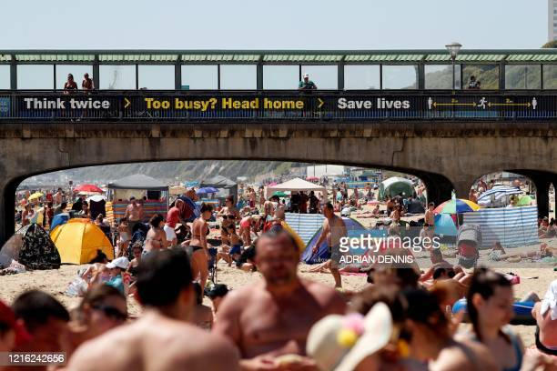 TOPSHOT Sunbathers enjoy the sunny weather on Boscombe beach in Bournemouth south England on May 30 as lockdown measures are eased during the novel...