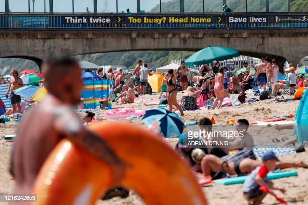 Sunbathers enjoy the sunny weather on Boscombe beach in Bournemouth, south England on May 30 as lockdown measures are eased during the novel...