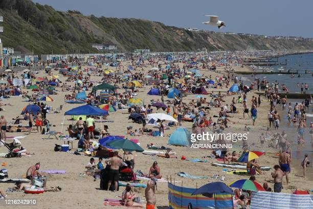 Sunbathers enjoy the sunny weather on Boscombe beach in Bournemouth, southern England on May 30 ahead of the coming into force of the first...
