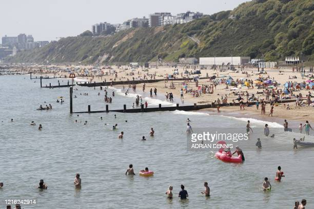 Sunbathers enjoy the sunny weather on Boscombe beach in Bournemouth southern England on May 30 ahead of the coming into force of the first...