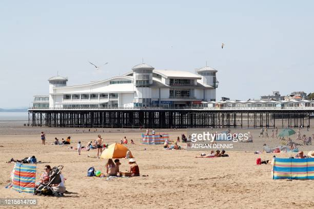 Sunbathers enjoy the warm weather at the beach in WestonsuperMare south west England on May 27 as lockdown measures are eased during the novel...