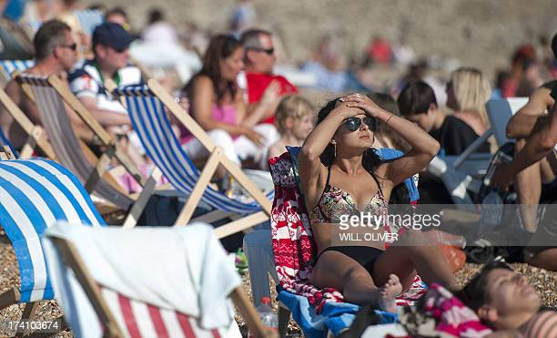 Sunbathers enjoying the late afternoon sunshine on the beach in Brighton on the south coast during hot weather on July 20th 2013 Britain has been...