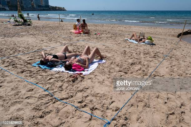Sunbathers in designated ropedoff areas enjoy a day out on Poniente Beach in Benidorm on June 21 a day after the town's beaches were reopened after...