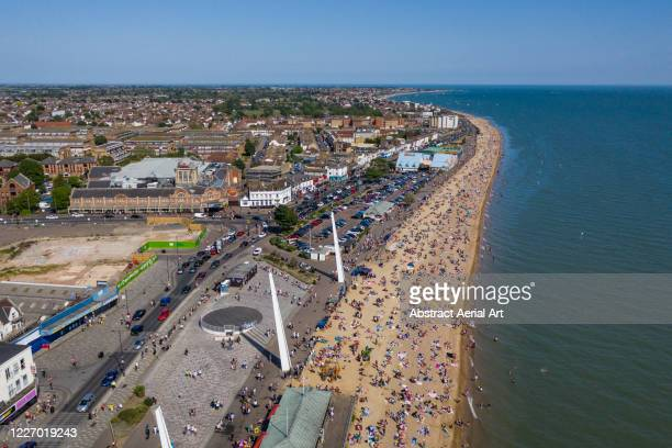 sunbathers on a beach during covid-19 pandemic, southend-on-sea, essex, united kingdom - southend on sea stock pictures, royalty-free photos & images