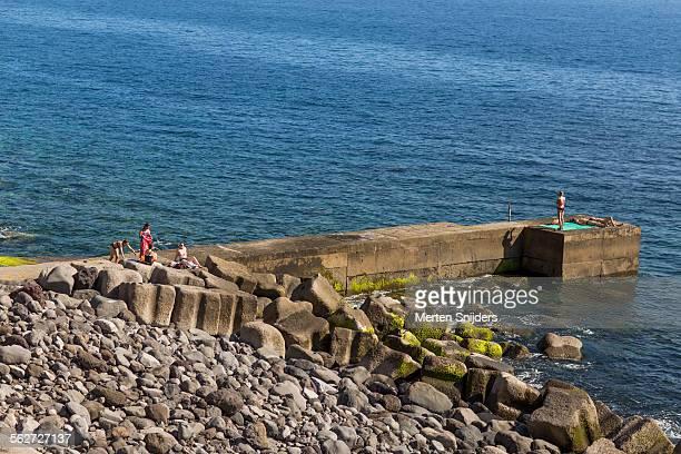 sunbathers on concrete pier at waterfront - merten snijders stockfoto's en -beelden