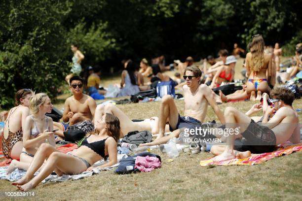 Sunbathers relax on Hampstead Heath in London on July 26 2018 Britain has been in the grip of its longest heatwave in decades sparking wildfires in...