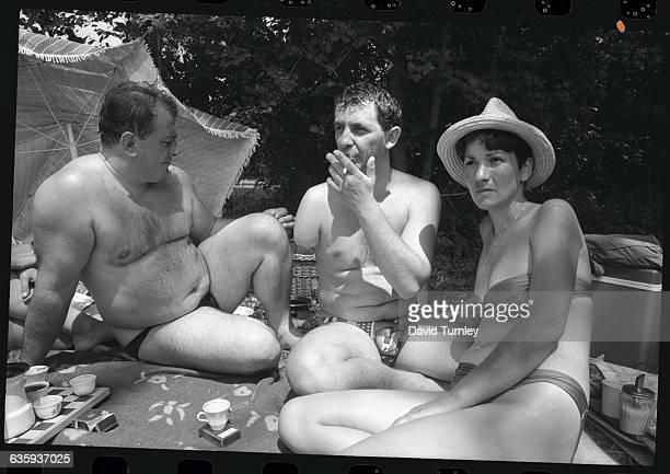 Sunbathers Relaxing Along a River