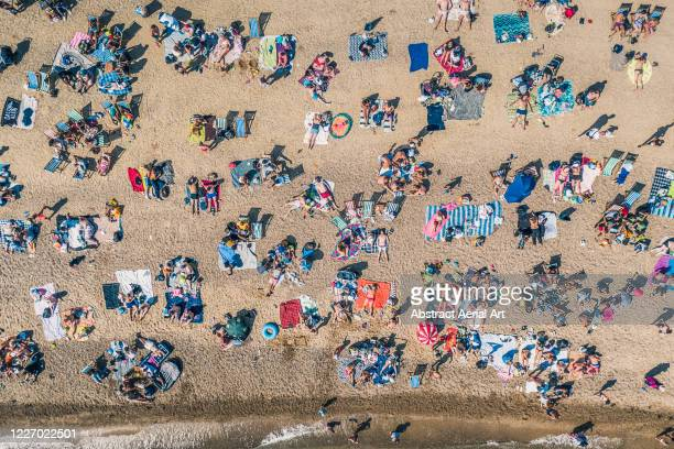 sunbathers relaxing on southend beach as seen from directly above, southend-on-sea, essex, united kingdom - coastline stock pictures, royalty-free photos & images