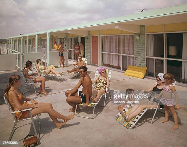 Sunbathers sit in deckchairs and chat on the sundeck of the Mardi Gras Motel, Virginia Beach, Virginia, 1960s.