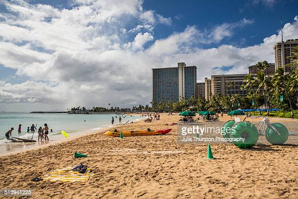 Sunbathers Snorkelers and Swimmers Frolic in the Sun and Play With Water Toys at The Tourist Vacation Travel Destination of Waikiki Beach Hawaii on...