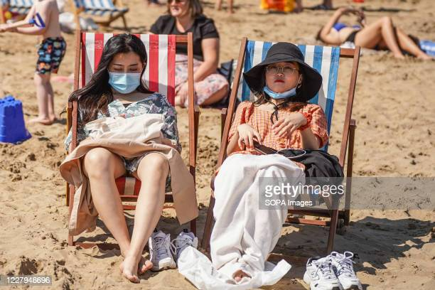 Sunbathers wearing face masks while sitting on deck chairs at South Bay beach during the hot weather