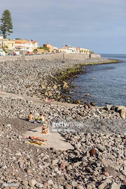 sunbathing at rocky beachfront - merten snijders stockfoto's en -beelden