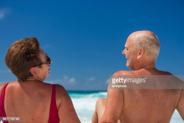 sunbathing best agers couple smiling at each other beach - medium shot stock pictures, royalty-free photos & images
