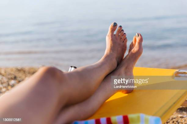 sunbathing on the beach - human foot stock pictures, royalty-free photos & images