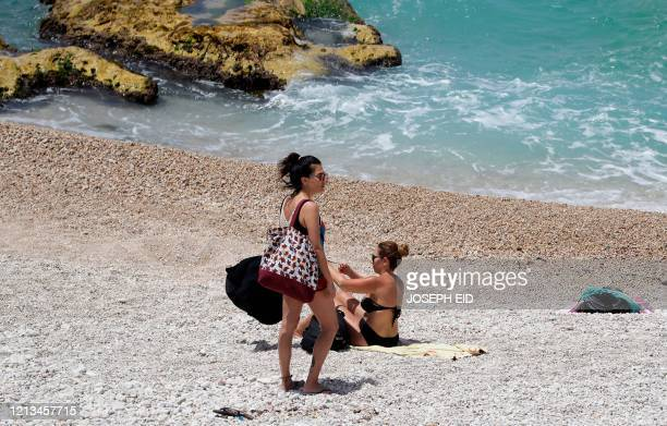 Sunbathing women prepare to pack their belongings as they are instructed to leave a beach in the village of Kfar Aabida in northern Lebanon on May 18...