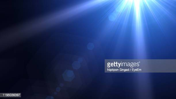 sunbeam against blue background - lens flare stock pictures, royalty-free photos & images