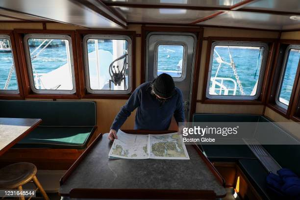 Sunbeam Engineer Storey King consults a map of Maines islands while approaching the harbor of Great Cranberry Island as captain Michael Johnson...