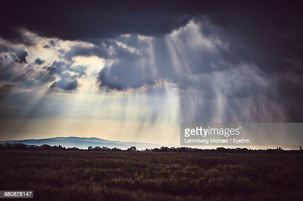 Sunbeam Streaming From Cloudy Sky Over Grassy Field