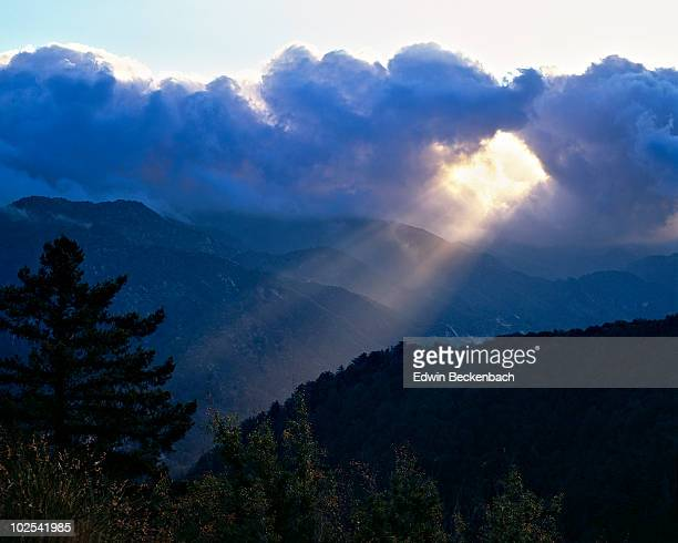 Sunbeam through clouds over mountains