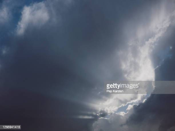 sunbeams breaking through thick clouds in sky - alpes maritimes stock pictures, royalty-free photos & images