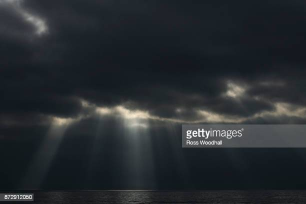 Sunbeams bursting from a storm cloud over the ocean