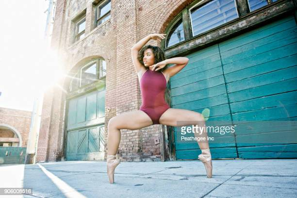 sunbeams on mixed race woman dancing in city - modern dancing stock pictures, royalty-free photos & images