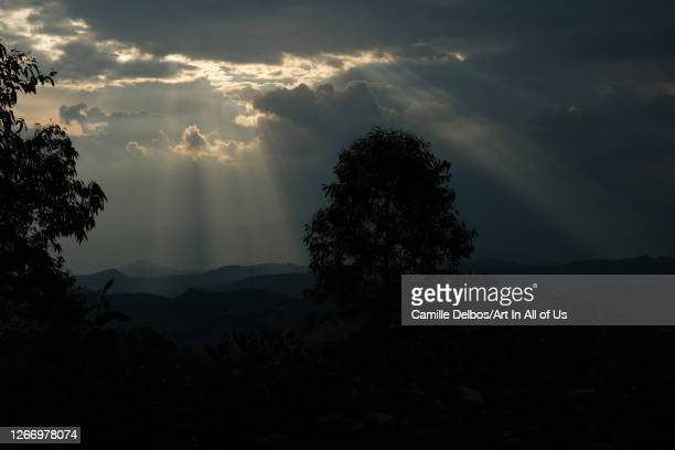 Sunbeams pierce the menacing clouds of thunderstorm over the hills of the countryside on Septembre 18 2018 in RN4 Northern Province Rwanda