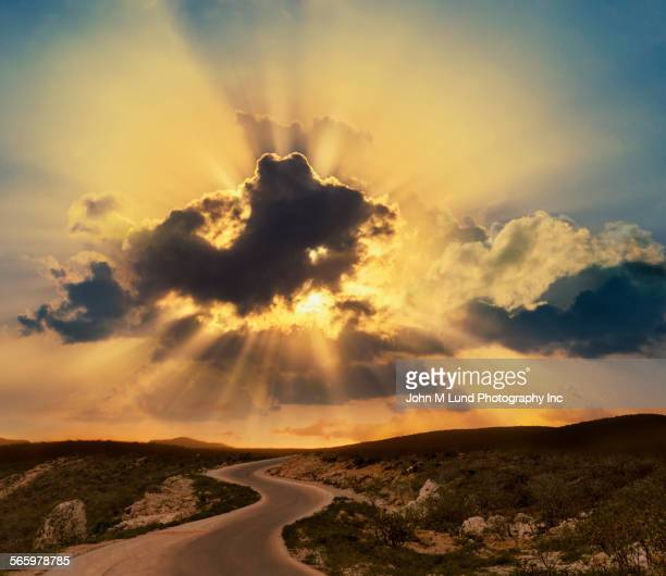 Sunbeams shining behind clouds over remote landscape