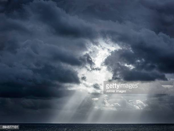 sunbeams shining through clouds - storm cloud stock pictures, royalty-free photos & images