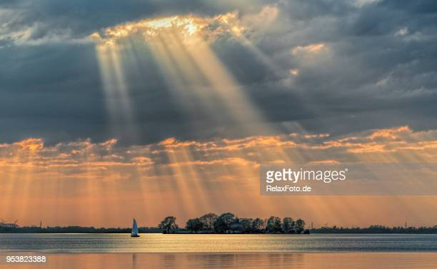 Sunbeams through cloudscape on lake.