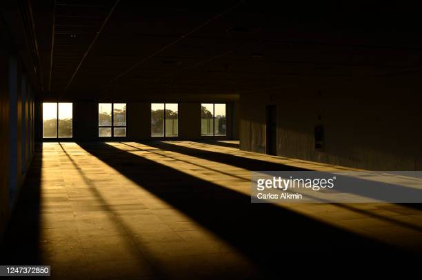 sunbeams through the windows of a large empty office room - licht natuurlijk fenomeen stockfoto's en -beelden