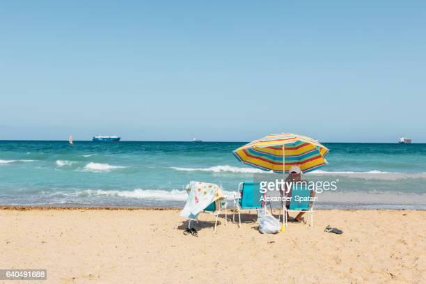 Sunbed and sun umbrella at El Saler wild beach near Valencia, Spain